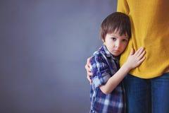 Piccolo bambino triste, ragazzo, abbracciante sua madre a casa immagini stock libere da diritti