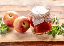 Piccolo barattolo di vetro pieno con l'inceppamento della mela e due mele e mente del greem su fondo di legno fotografia stock