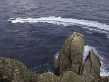 Piccolo barca con la scia dell'elica con nelle rocce della priorità alta fotografia stock libera da diritti
