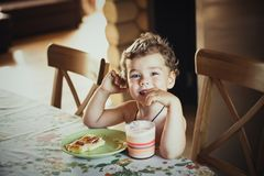 Piccolo bello ragazzo sorridente sveglio che si siede alla tavola Torta sul piatto verde e su un bicchiere di latte davanti lui L fotografia stock