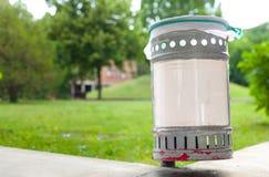 Piccolo bidone della spazzatura del ferro in parco pubblico con l'ed di plastica bianco del segno immagine stock libera da diritti