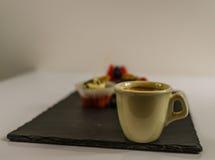 Piccolo caffè nero in una tazza della porcellana su un piatto di pietra nero fotografia stock libera da diritti
