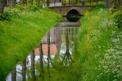 Piccolo canale con l'acqua corrente, i grandi alberi ed i lati dell'erba verde in vecchia città Heusden, il Brabante Settentriona fotografie stock libere da diritti