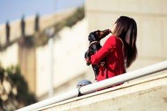 Piccolo cane sveglio che bacia bella giovane donna mentre camminando alla via fotografia stock libera da diritti