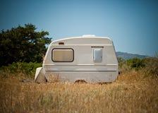 Piccolo caravan parcheggiato nel campo fotografia stock
