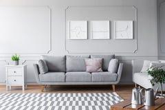 Piccolo cassettone bianco con la pianta verde in vaso grigio sopra a accanto allo strato comodo con i cuscini in salone scandinav fotografia stock