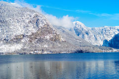 Piccolo castello su una costa del lago vicino alle montagne Immagine Stock