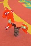 Piccolo cavaliere variopinto della molla del cavallino nel campo da giuoco dei bambini Immagine Stock Libera da Diritti
