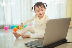 Piccolo computer portatile asiatico del gioco della ragazza nella casa Fotografia Stock