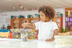 Piccolo concentrato della ragazza del bambino sul disegno Ragazza africana della miscela imparare e giocare nella classe della sc fotografia stock