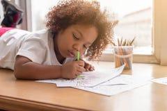 Piccolo concentrato di indicazione della ragazza del bambino sul disegno Ragazza africana della miscela imparare e giocare nella  fotografie stock libere da diritti