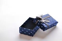 Piccolo contenitore di regalo blu aperto con il nastro ed i cerchi Fotografia Stock