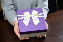 Piccolo contenitore di regalo porpora con il nastro in mani della donna Per le madri D fotografia stock