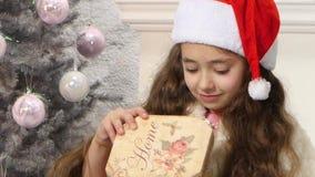 Piccolo contenitore di regalo sveglio di Natale di apertura della ragazza video d archivio