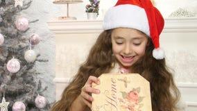 Piccolo contenitore di regalo sveglio di Natale di apertura della ragazza stock footage