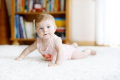 Piccolo corpo portante divertente della neonata ed imparare strisciare immagini stock libere da diritti
