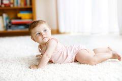 Piccolo corpo portante divertente della neonata ed imparare strisciare fotografie stock libere da diritti