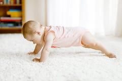 Piccolo corpo portante divertente della neonata ed imparare strisciare fotografia stock