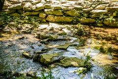 Piccolo corso d'acqua allineato con la pietra della montagna Fotografia Stock