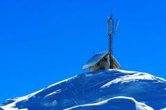 Piccolo cottage con le antenne di comunicazione sulla cima della montagna Fotografia Stock