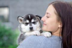 Piccolo cucciolo grazioso del husky all'aperto in mani della donna fotografia stock