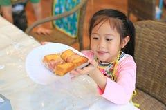 Piccolo cuoco unico che mostra il bacon del pane inzuppato in latte/uova e zucchero e fritto in padella immagini stock libere da diritti