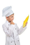 Piccolo cuoco unico che pensa del che piatto potrebbe fare con cereale, isolato su bianco Immagine Stock