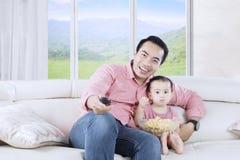 Piccolo derivato e padre che guardano TV immagine stock
