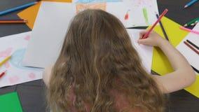 Piccolo disegno della ragazza con le matite variopinte nella sua stanza, sviluppo artistico stock footage
