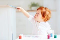 Piccolo disegno felice dell'artista del bambino con le pitture variopinte a casa immagini stock