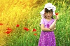 Piccolo dispiaceva e scontentato la ragazza sveglia con il fiore rosso Fotografie Stock Libere da Diritti