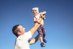 Piccolo divertimento della figlia del padre come ritratto di stile di vita della famiglia davanti a cielo blu fotografie stock