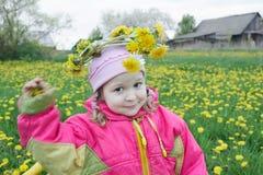 Piccolo due anni della ragazza che giudica la corona floreale fatta dei denti di leone gialli in tensione fiorisce Fotografia Stock Libera da Diritti