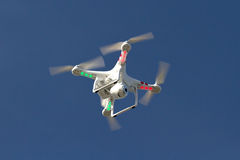 Piccolo elicottero senza equipaggio con una macchina fotografica che galleggia nel cielo Immagini Stock