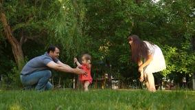 Piccolo figlia va dalla mamma al papà su erba verde in un parco in primavera, l'estate Concetto 'nucleo familiare' felice il bamb archivi video