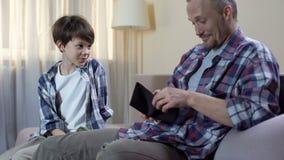 Piccolo figlio che elemosina padre dare più denaro per piccole spese, bisogni finanziari, paternità stock footage