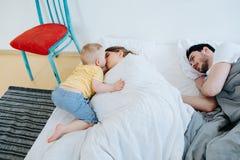 Piccolo figlio sveglio che prova a svegliare i suoi genitori fotografia stock