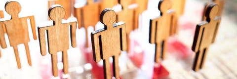 Piccolo figure di legno della gente del giocattolo sta nella fila immagini stock libere da diritti