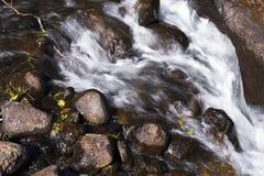 Piccolo fiume della montagna che circola sull'esposizione lunga delle rocce fotografia stock libera da diritti