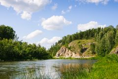 Piccolo fiume in terre selvagge fra le colline invase dalla foresta alla somma fotografia stock