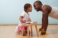 Piccolo forma fisica della figlia che forma suo padre Fabbricazione delle note Gioco di ruolo del bambino fotografia stock