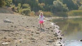 Piccolo funzionamento sveglio della ragazza lungo il lago vicino al stock footage