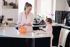 Piccolo genitore d'aiuto del bambino adorabile con pasta alla cucina immagini stock