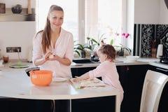 Piccolo genitore d'aiuto del bambino adorabile con pasta alla cucina immagini stock libere da diritti