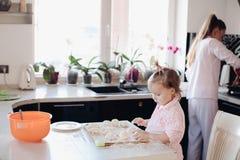 Piccolo genitore d'aiuto del bambino adorabile con pasta alla cucina fotografia stock