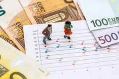 Piccolo gioca la gente per discutere il grafico e l'euro immagini stock