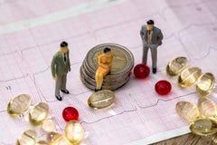 Piccolo gioca la gente per trovare sulle euro monete e sul cardiogramma fra le pillole fotografia stock