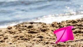 Piccolo giocattolo del secchio della sabbia sulla spiaggia di estate Fotografie Stock