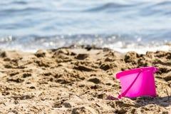 Piccolo giocattolo del secchio della sabbia sulla spiaggia di estate Fotografie Stock Libere da Diritti