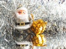 Piccolo giocattolo Santa Claus con i regali su un fondo d'argento luminoso brillante Fotografia Stock